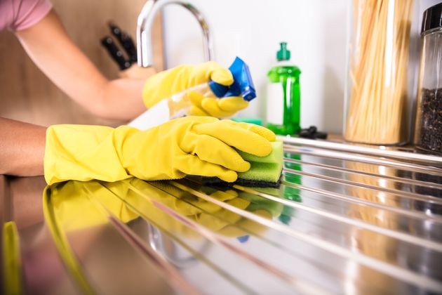 Close-up Of Person's Hand Wearing Yellow Gloves Cleaning Stainless Steel Sink With