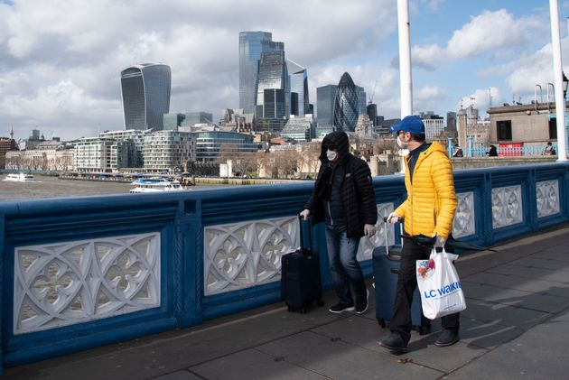 Tourists wear surgical masks on Tower Bridge during the Coronavirus outbreak in