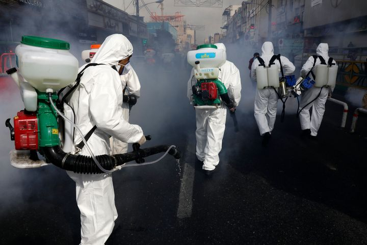 Firefighters disinfect a street against the new coronavirus, in western Tehran, Iran, Friday, March 13, 2020. (AP Photo/Vahid