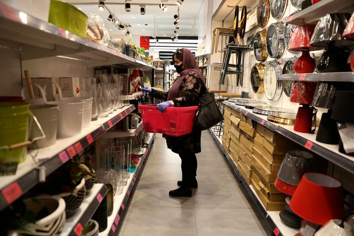 A woman wearing a face mask shops at a store in Bamland shopping mall, in Western Tehran, Iran, Sunday, March 15, 2020. (AP P
