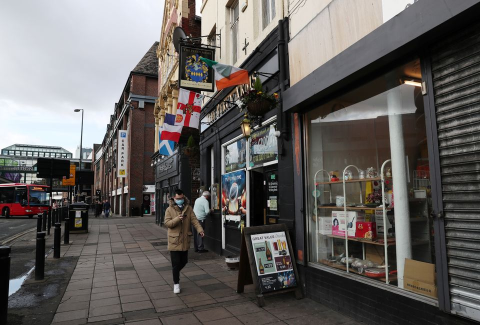A general view as a man wearing a protective face mask walks past the Percy Arms pub,