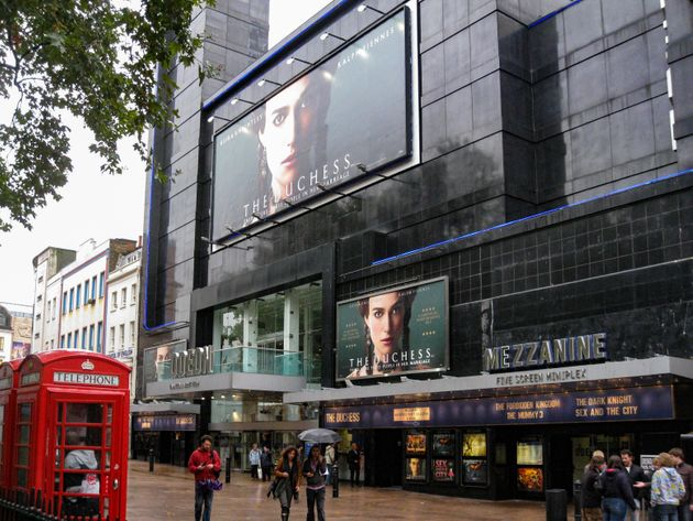 The facade of the modern Odeon Cinema and the typical red telephone booths in Leicester Square, London,