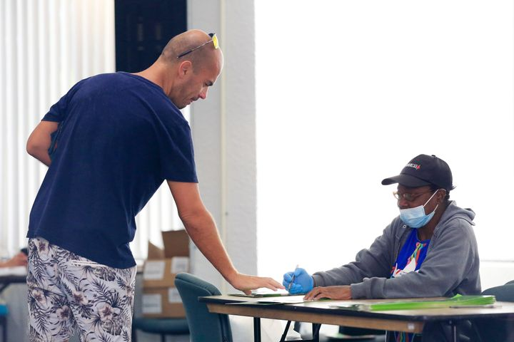 A poll worker provides a voter with a ballot during the Florida presidential primary on March 17, 2020, in Miami.