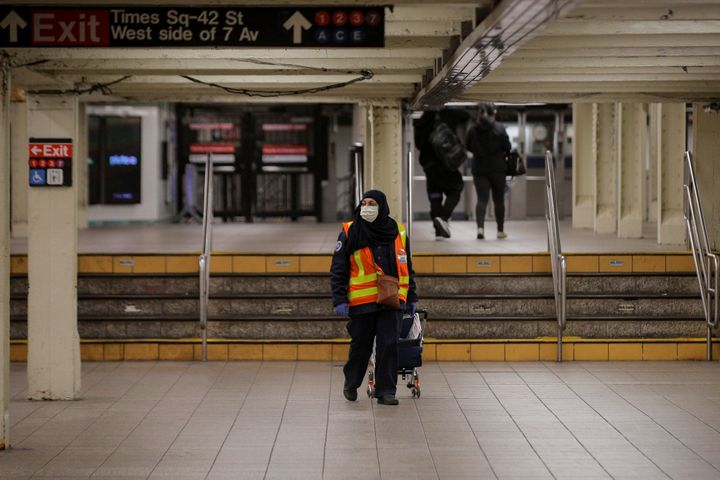 An MTA transit worker walks through a nearly empty Times Square - 42nd St. subway station during the morning rush in New York