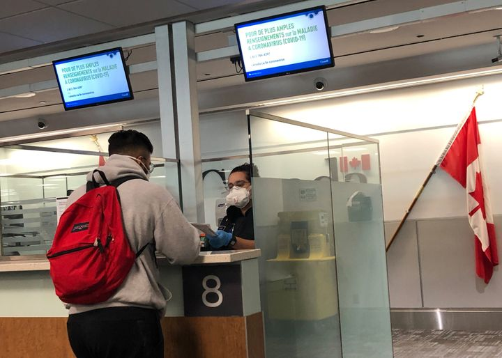 A Canada Border Services Agency officer wears a protective face mask amid coronavirus fears as she checks passports for those arriving at Toronto Pearson International Airport in Toronto on March 15, 2020.