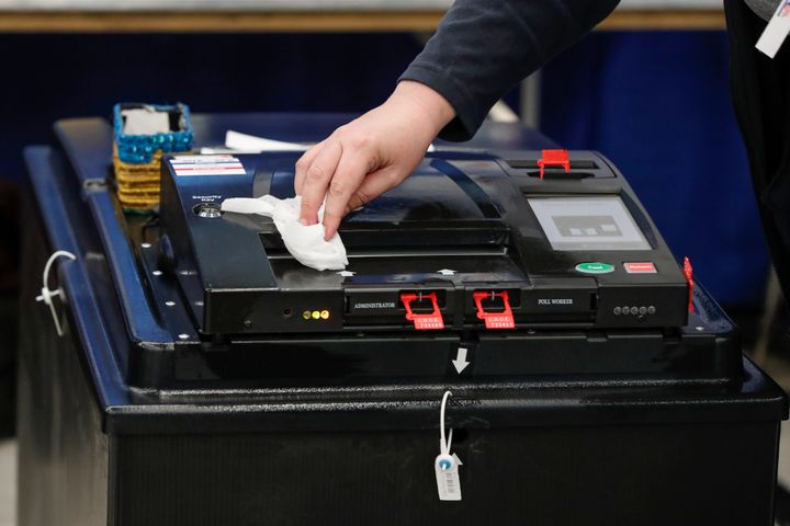 An election official cleaned a voting machine in Chicago as Illinois proceeded with its presidential primary on Tuesday.