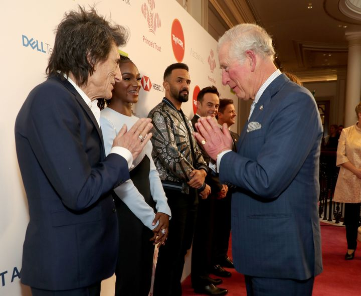 Charles uses a Namaste gesture to greet Rolling Stone Ronnie Wood as he attends the Prince's Trust and TK Maxx & Homesens