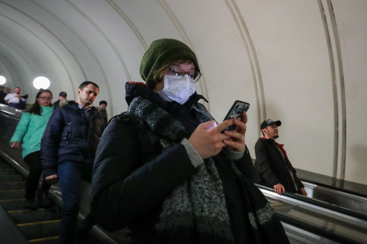 A woman wears a face mask while using her cellphone as she enters a Moscow Underground station during the coronavirus pandemi