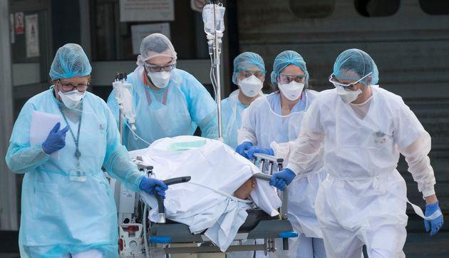 Du personnel médical transporte un patient atteint du coronavirus vers un hélicoptère à l'hôpital Emile...