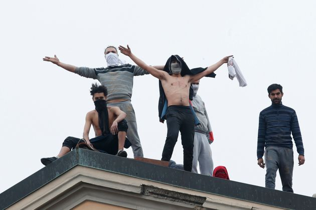 Inmates stand on the roof of the San Vittore prison to protest after restrictions that were imposed on...
