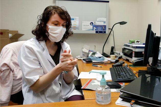 À Paris le 17 mars 2020, un médecin portant un masque de protection utilise du gel hydro-alcoolique...