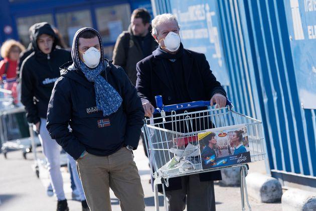 Des Belges masqués face au coronavirus font leurs courses à Bruxelles le 18 mars