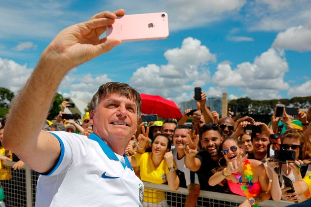 Brazilian President Jair Bolsonaro takes a selfie with supporters in front of the Planalto Palace on...