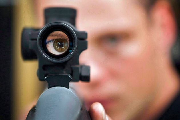 In this file photo, an employee looks through the scope of long gun at a store in Calgary, Alta., Sept....