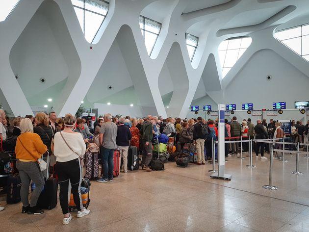 Des passagers patientent à l'aéroport de Marrakech le 15 mars, alors que les vols internationaux...