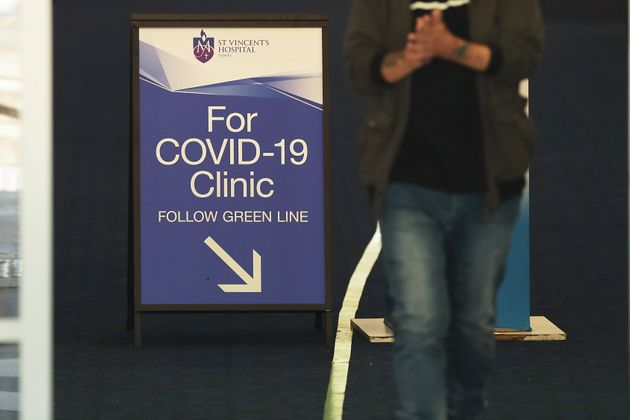 People pass signs for a COVID -19 Clinic at St Vincent's hospital on March 18, 2020 in Sydney,