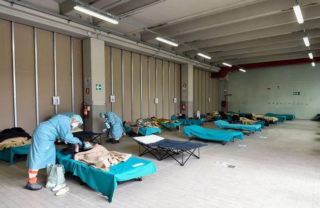 의료진이 임시로 마련된 병상에서 코로나19 환자들을 치료하고 있다. 브레시아, 이탈리아. 2020년