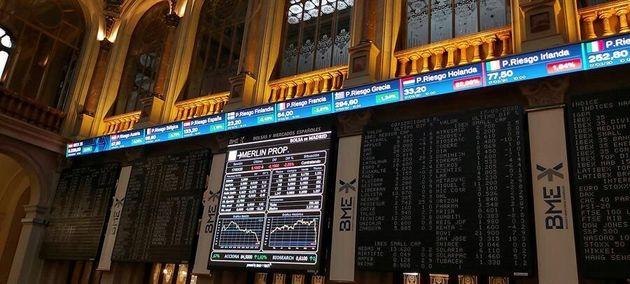 Una pantalla (c) muestra un gráfico con la evolución de uno de los valores que cotiza en la Bolsa de