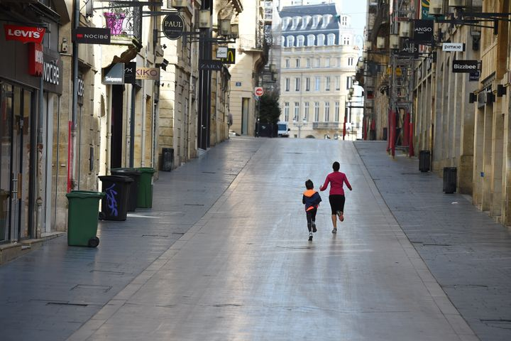 A woman and her son run in the deserted Sainte-Catherine street in Bordeaux, southwestern France