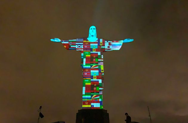 Flags of the countries affected by the spread of the new coronavirus are projected on the Christ the...