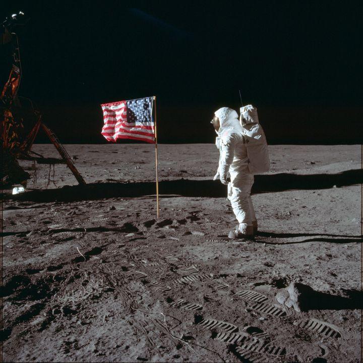 Buzz Aldrin faces the flag on the moon.