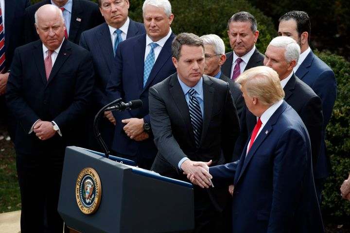President Donald Trump shakes hands with Doug McMillon, president and CEO of Walmart Inc., during a news conference about the