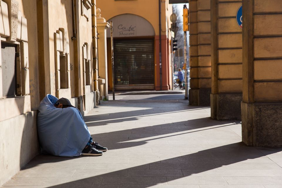 A homeless person sleeping under porches in Bologna during Italy's