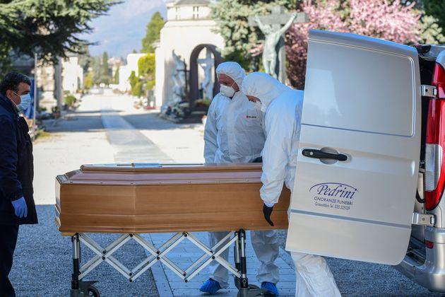Agentes usando máscara levam caixão para cemitério de Bergamo, na