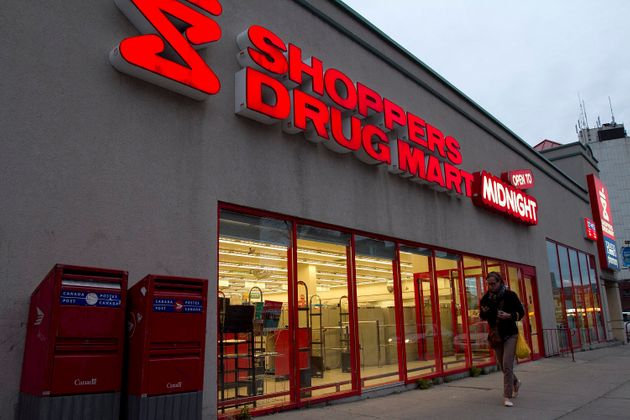 In this file photo, a woman walks in front of a Shoppers Drug Mart in Kingston, Ont., Mon. April 30,