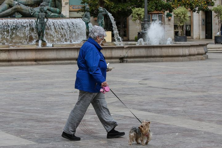 A woman walks her dog in Valencia, Spain. Experts say going for walks is safe, as long as you're not getting too close to people.