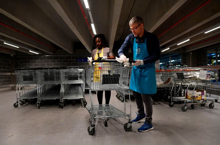 Members of a supermarket in Belgium disinfect a trolley to help stop the spread of the coronavirus.