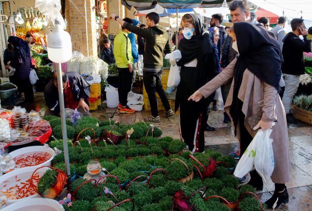 Iranians, some wearing protective face masks, shop at a bazaar ahead of Nowruz in the capital Tehran...