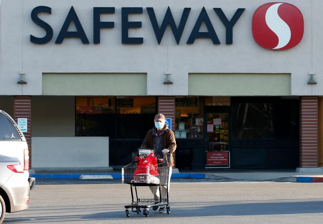 Wearing a mask for protection against the coronavirus, Henry Powell, heads to his car after shopping...