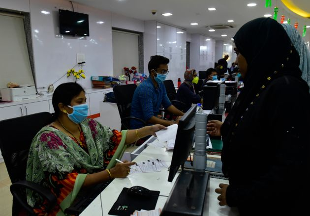 MStaff of Bank of Baroda wear protective mask while working in bank at Byculla because of Corona pandemic,...