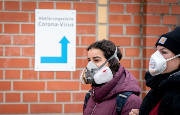 20 March 2020, Berlin: Mother and daughter pass a sign in front of a Berlin clinic with a mouthguard,...