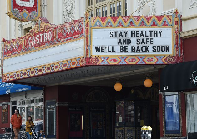 A couple walks by the Castro theater with their baby in San Francisco, California on March 17,