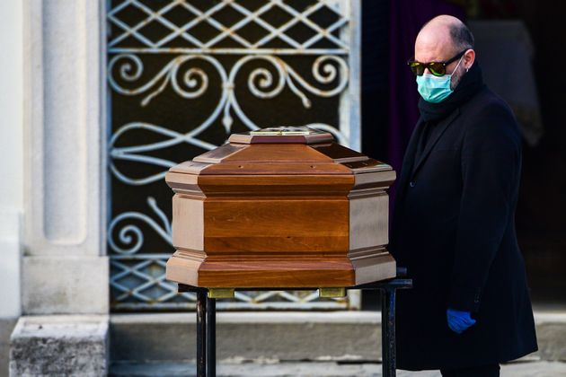 A man wearing a face mask stands by the coffin of his mother during a funeral service in the closed cemetery...