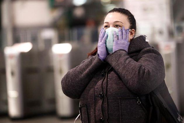 Una mujer con mascarilla y guantes en