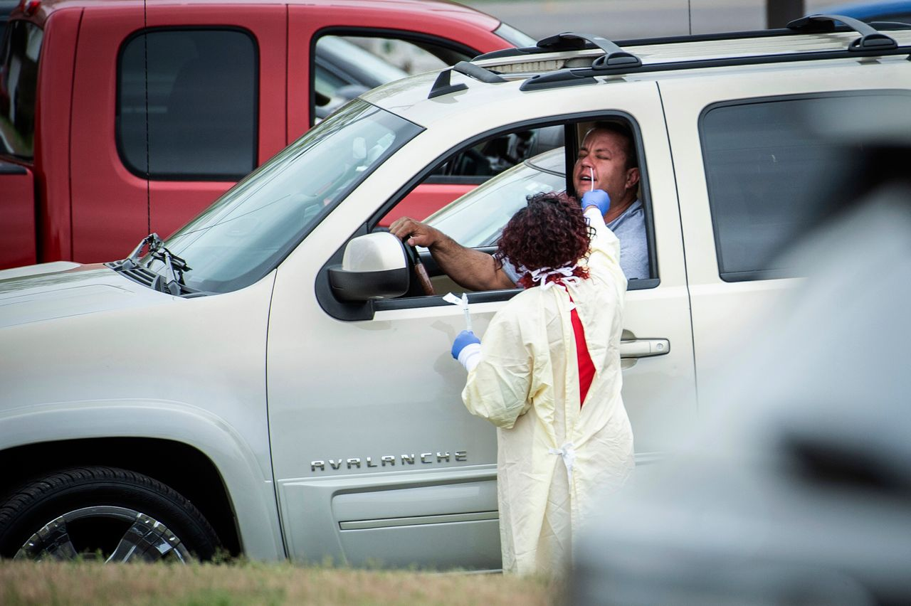A drive-through patient has his nose swabbed by staff during a screening at Waddell Family Medicine as Athens-Limestone Hospital opens a flu and fever clinic Thursday in Athens, Ala. Patients will only be tested for COVID-19 if indicated by their exam or ordered by a physician or provider.