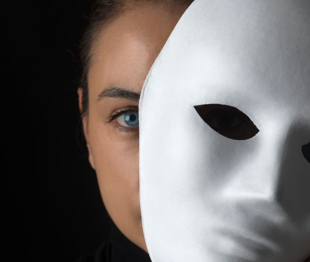 Female is hiding her face behind a white mask on black