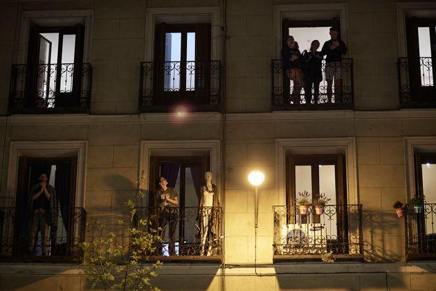 Varias personas en Madrid se asoman a los balcones durante el confinamiento por la pandemia de