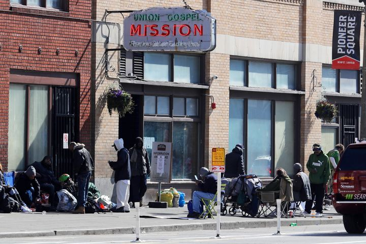 People gather on the sidewalk in front of the Union Gospel Mission in downtown Seattle on Friday. The mission serves a large