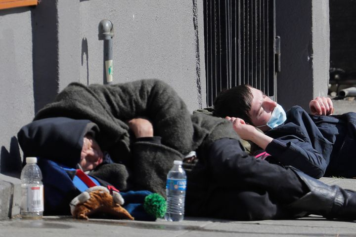 A man wearing a mask sleeps near another person on a sidewalk near the Union Gospel Mission on Friday.