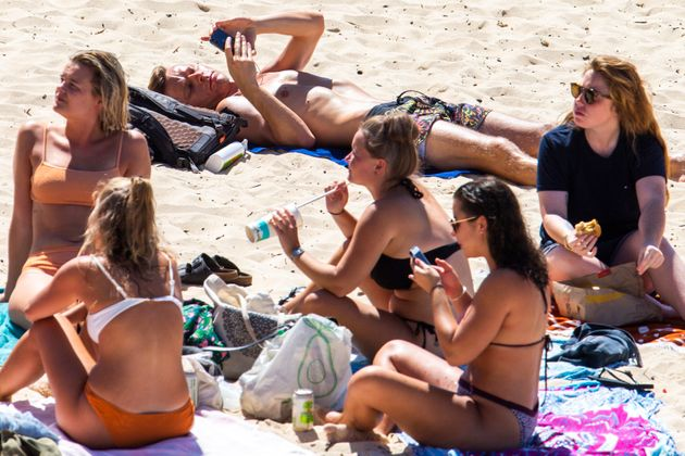 People are seen sitting close together at Bondi Beach on March 20, 2020 in Sydney,