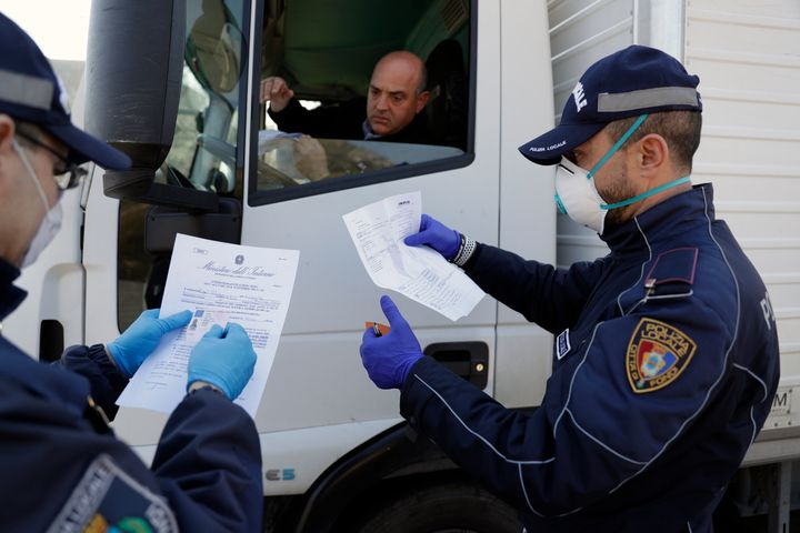 City police officers check a truck driver in Fondi, near Rome, Friday, March 20, 2020. A farm town which has the largest whol