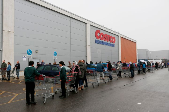 Customers wait in a long queue to enter a Costco outlet in Farnborough, west of London, England. March 19, 2020.