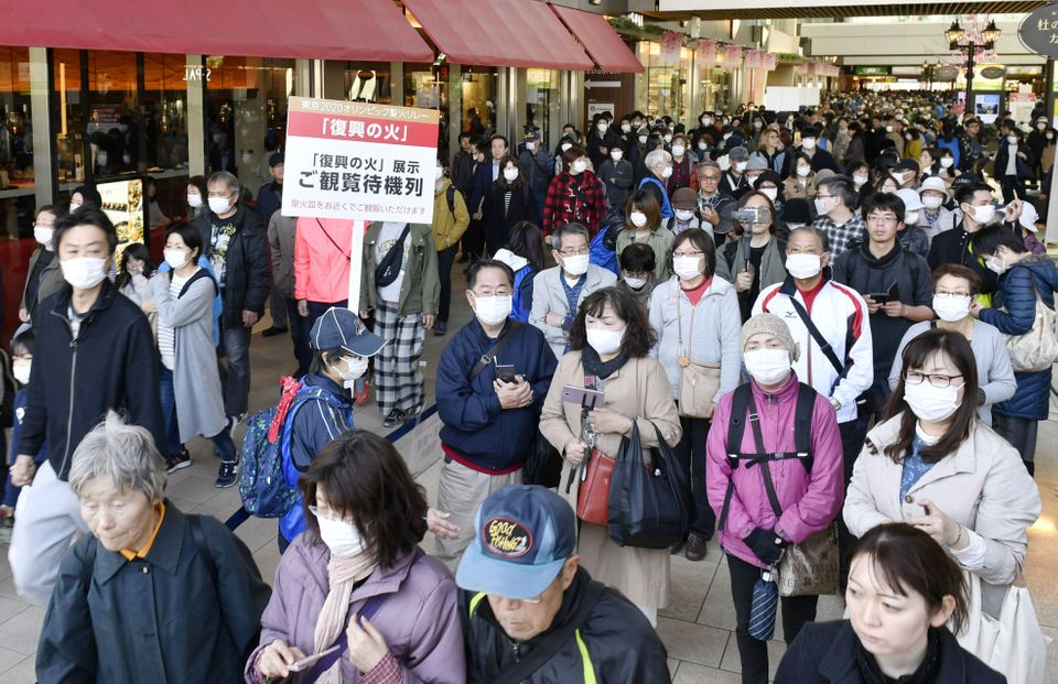 People wearing protective face masks queue as they try to watch the Olympic cauldron during the Tokyo...