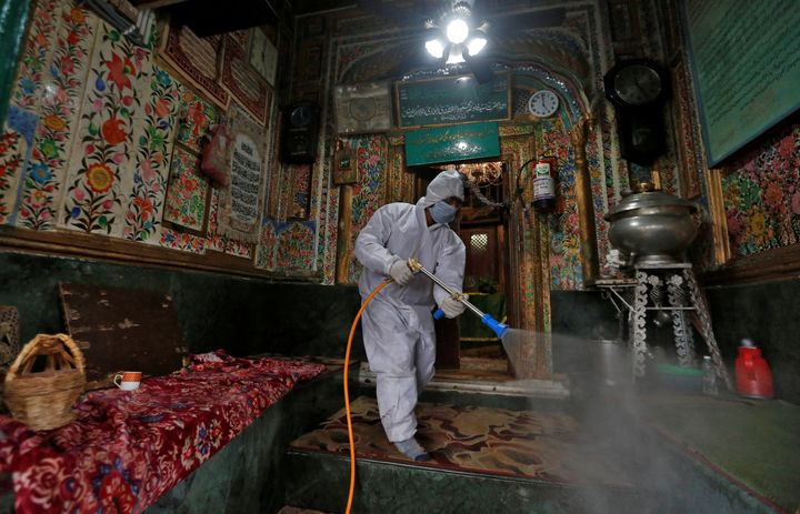 A municipal worker wearing a protective suit disinfects the shrine of Sufi Saint Khawaja Naqashband as a preventive measure against the spread of coronavirus disease (COVID-19), in Srinagar March 19, 2020.