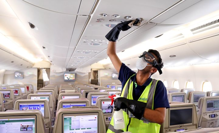 A member of cleaning staff wearing protective mask disinfects air vents of an Emirates Airbus A380 in Dubai, United Arab Emirates, on March 5.