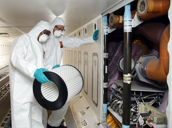 Members of cleaning staff in protective suits change air filters on an Emirates aircraft as part of disinfectant measures against the coronavirus.